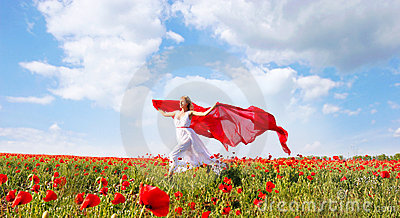 Happy woman with red scarf in poppy field