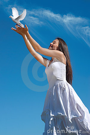 Happy woman releasing a pigeon in sky