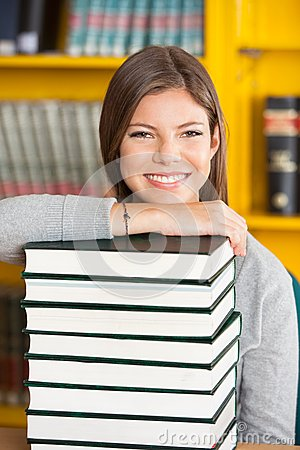 Happy Woman Resting Chin On Stacked Books In