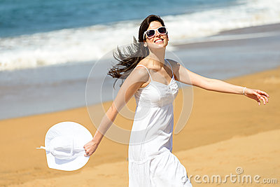 Happy woman running and dancing on beach