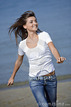 Happy woman running windblown on the beach