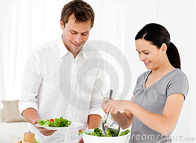 Happy woman serving salad to his boyfriend