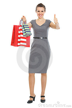 Happy woman with shopping bags showing thumbs up