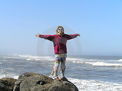 Happy woman on the shore of the ocean