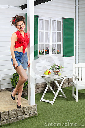 Happy woman in shorts poses next country house