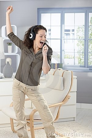 Happy woman singing with headphones