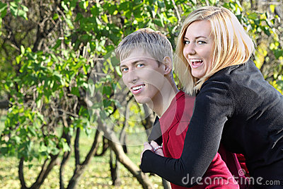Happy woman sits on back of man and laughs in park