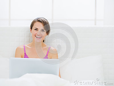 Happy woman sitting on bed and working on laptop