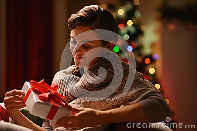 Happy woman sitting chair with Christmas present