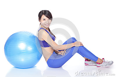 Happy woman sitting on floor with fit ball