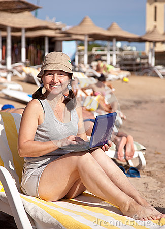 Happy woman sitting  with laptop at  beach