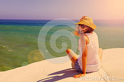 Happy woman sitting on the seaside