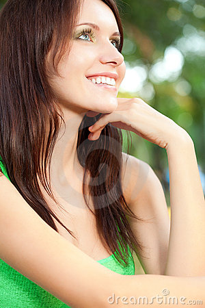 Happy woman sitting under the tree closeup face