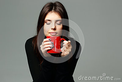 Happy woman smelling the aroma of coffee