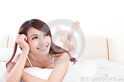 Happy woman smile while lying on the bed