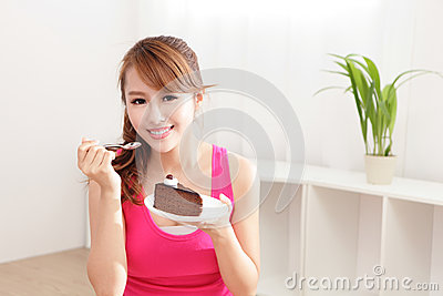 Happy woman smiles eating chocolate cake