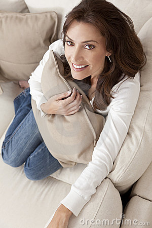 Happy Woman Smiling Holding Cushion At Home