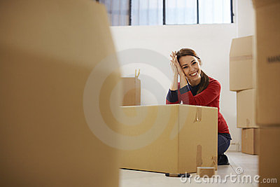 Happy woman smiling at home during move with boxes