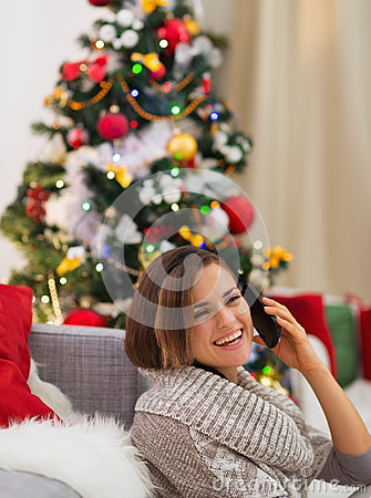 Happy woman speaking mobile near Christmas tree