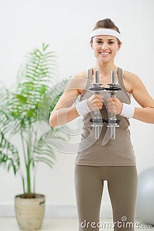 Happy woman in sportswear holding dumbbells