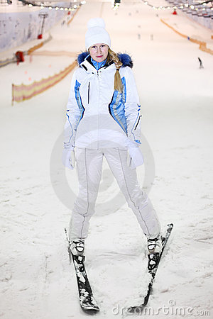 Happy woman stands on ski in indoor ski