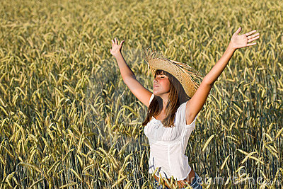Happy woman with straw hat enjoy sun in field