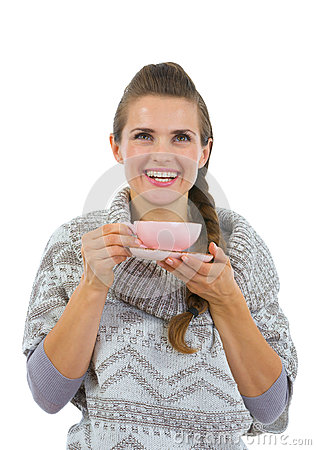 Happy woman in sweater having hot beverage