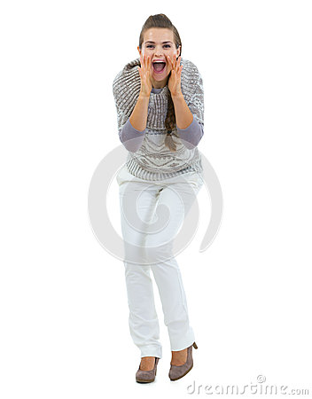 Happy woman in sweater shouting through megaphone shaped hands