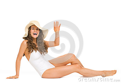 Happy woman in swimsuit and hat laying on floor