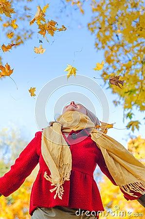Happy woman throwing leaves.