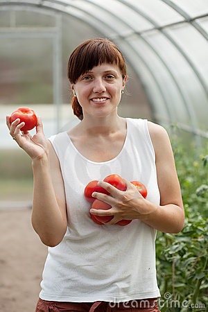 Happy  woman with tomato harvest
