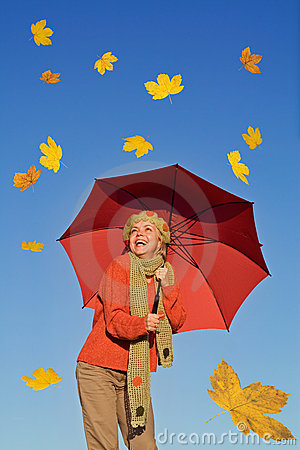 Happy woman with umbrella and falling leaves