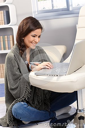 Happy woman under blanket with laptop