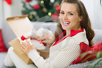 Happy woman unpacking parcel with Christmas gift