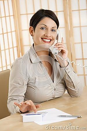 Happy woman using calculator