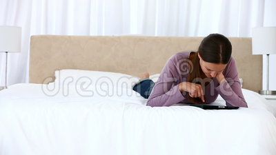 Happy woman using a computer tablet lying on the bed Stock Photo