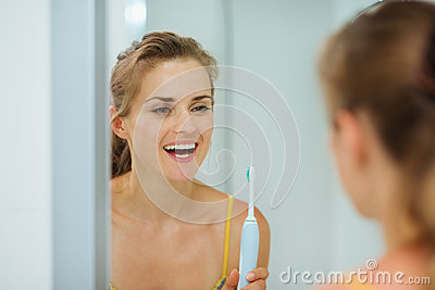 Happy woman using electric toothbrush in bathroom