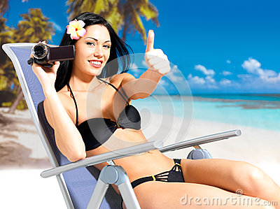 Happy woman with a video camera on beach
