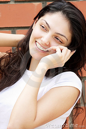 Happy woman at wall talking cellphone