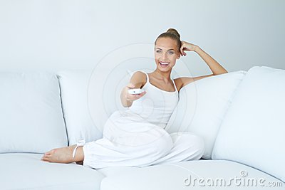 Happy woman watching tv on sofa