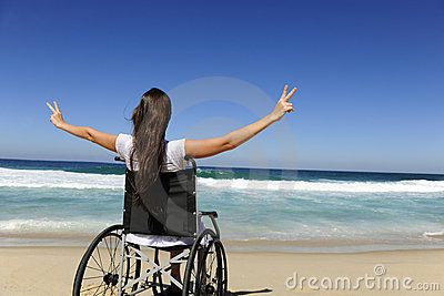 Happy woman in wheelchair showing victory sign