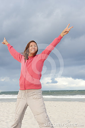 Happy woman in winning pose at beach