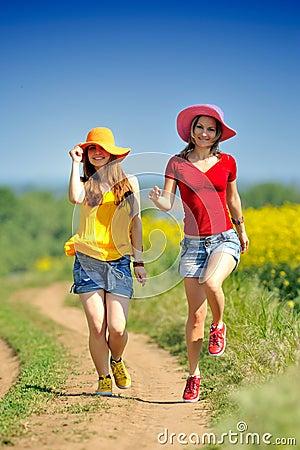 Happy women on blooming rape field in summer