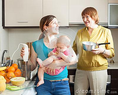 Happy women with child together cooking fruit puree