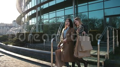 Happy women coming out of shopping mall with bags stock video