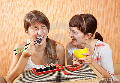 Happy women eating sushi rolls