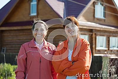 Happy women  in front of  home