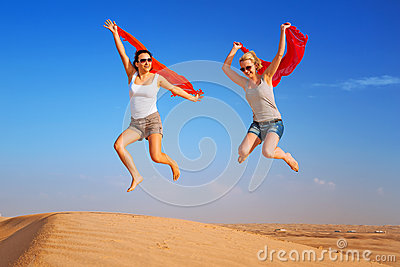 Happy women jumping in the desert