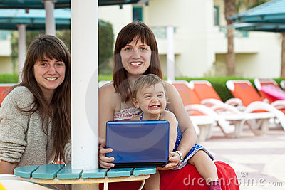 Happy women with laptop   at resort hotel