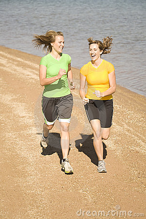 Happy women running on beach